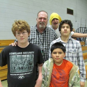Rob McKeown, Scotts Mills teacher's aid and boys basket ball coach takes a break from P.E. for a picture with students.