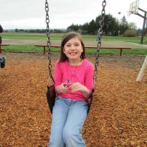 Makenna Neukomm, grade 2 has fun on the swings at Pratum School during recess.