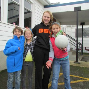 (From left) Third graders Emily Rattray and Kailee Bode visit with Garce Haury, grade 8 and her little sister Alexis, grade 3 during recess at Pratum School.