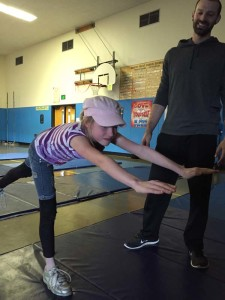 "Kaitriana McElfresh, grade 6 demonstrates the ""airplane"", her favorite yoga pose in P.E. class at Robert Frost School."