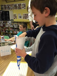 "Kindergartener Levi Mandish puts cotton balls in a cone he made for the annual ""Egg Drop"" lesson at Evergreen School."