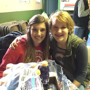Eighth graders Katlyn Veeck (Ueeck) (left) and Abigail Koch take a minute during a parent-provided hot lunch to share what they like best about their school.