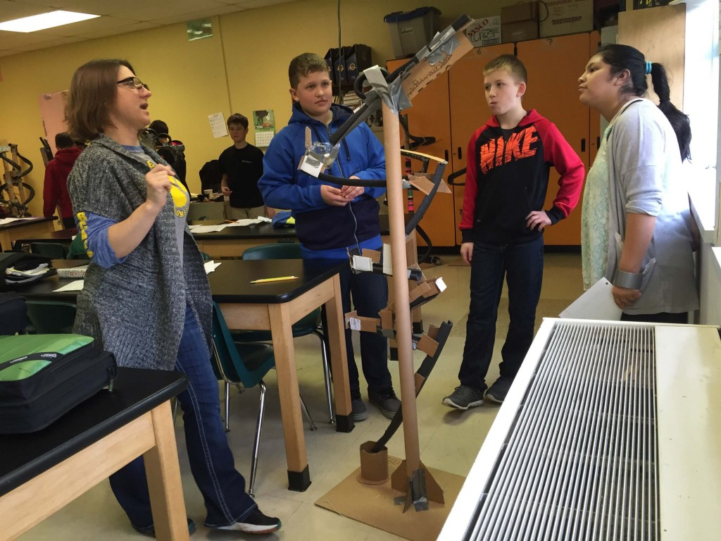 Butte Creek Teacher Stacie Watts helps students test their model roller coasters. (From left) Emilian Larionov, Zach Kuenzi, and Mayra Torralba