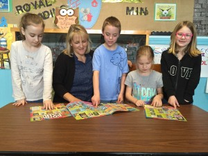 Office Manager Debbie Wiesner looks at book fair choices with students from Eugene Field School.