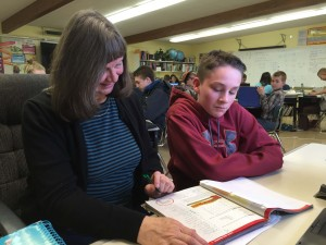 Educational Assistant Debbie Baggett looks over a workbook with Evergreen 7th grader Colby Henckel.
