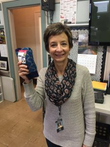 Pratum teacher Dawn Roth holds a pair of socks donated through a sock drive organized by students in grades 6, 7 and 8.
