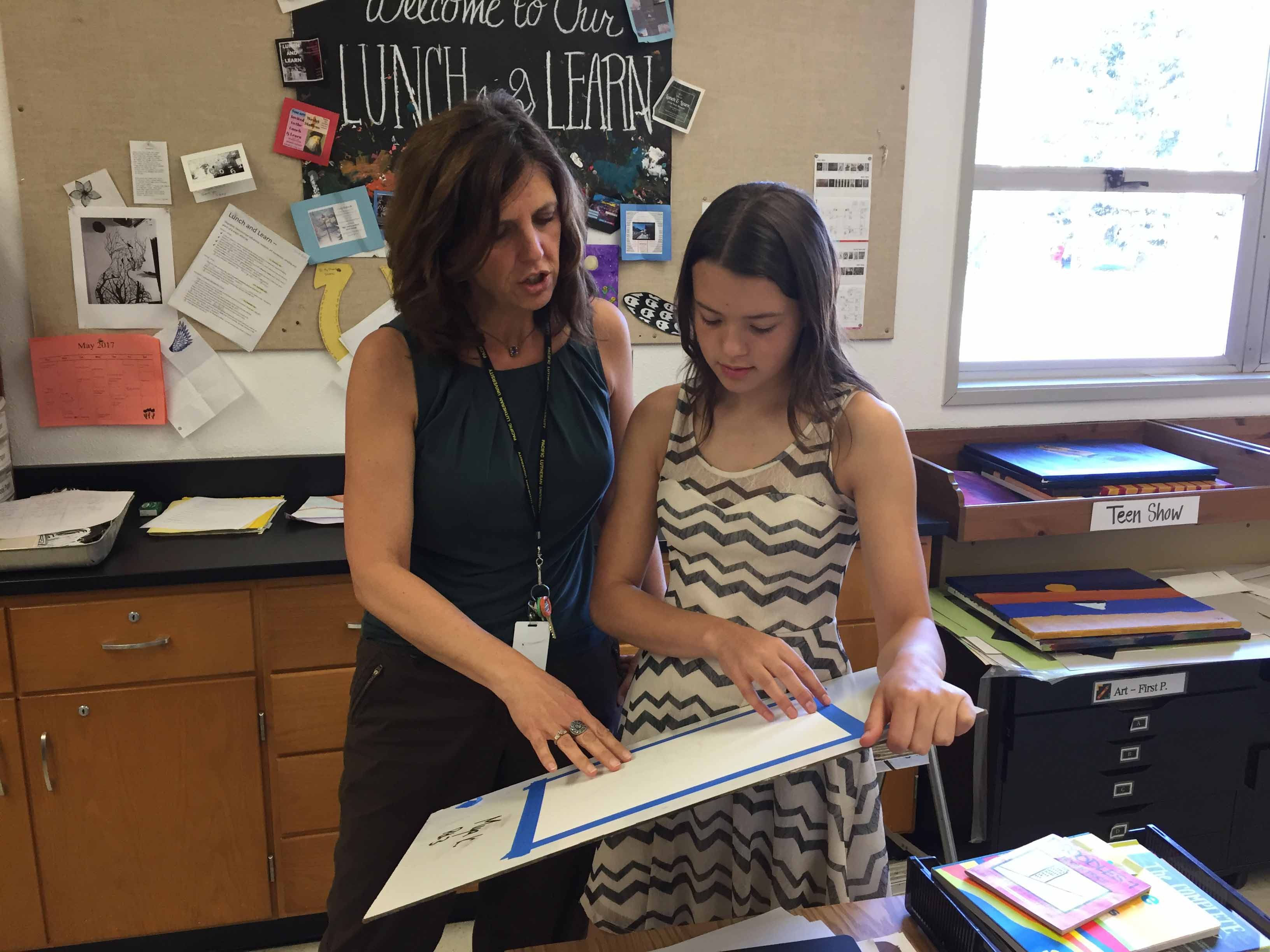 Art teacher Shana Chandler talks with Mya Kuzmin, grade 8, about composition during advanced art class at SMS.