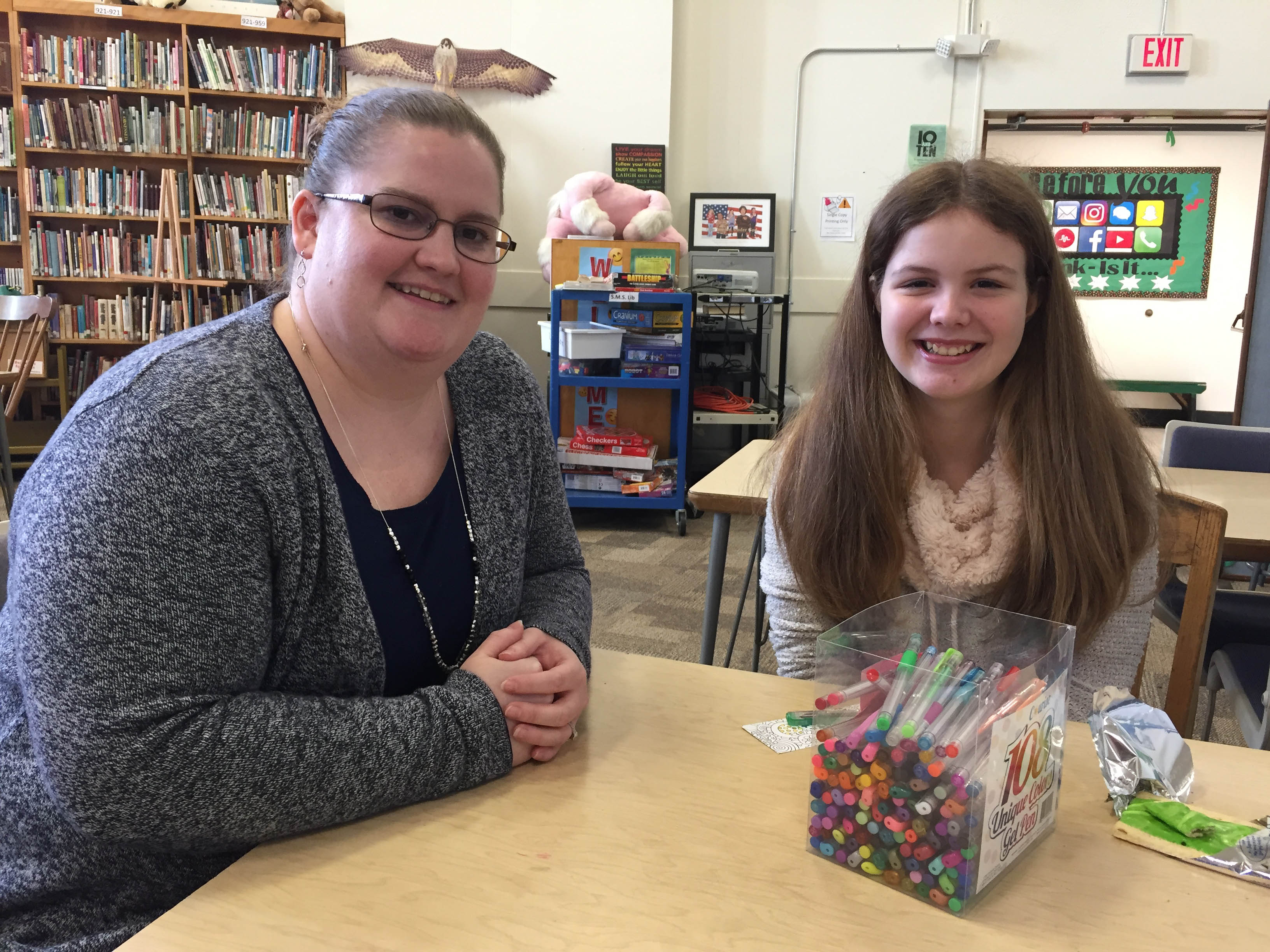 SMS School Counselor Hillary Parksion stops to visit with Grace Dover, grade 7, in the school library.