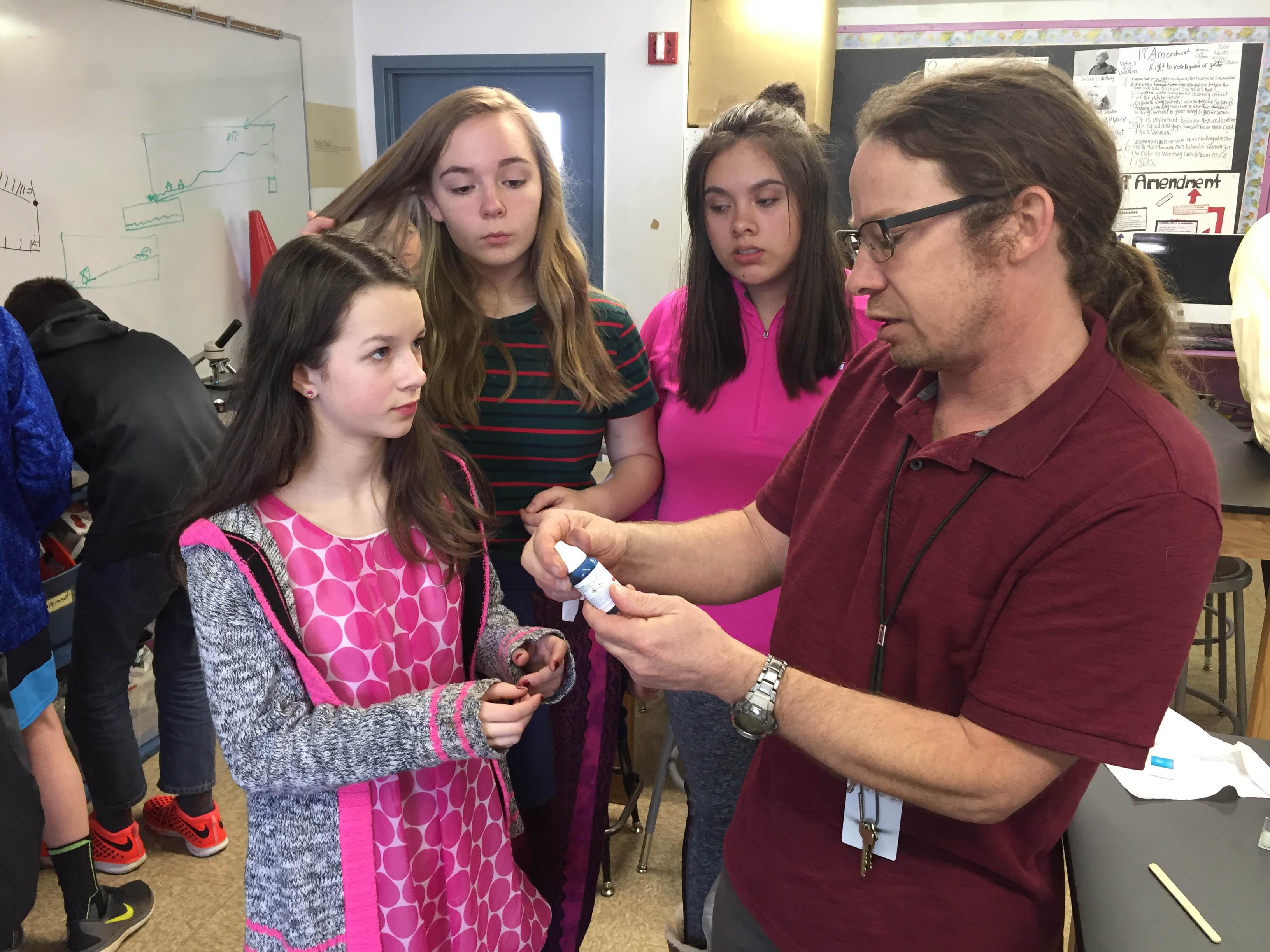 Silver Crest science and social studies teacher Dan Feller helps students prepare to examine slides of skin cells.