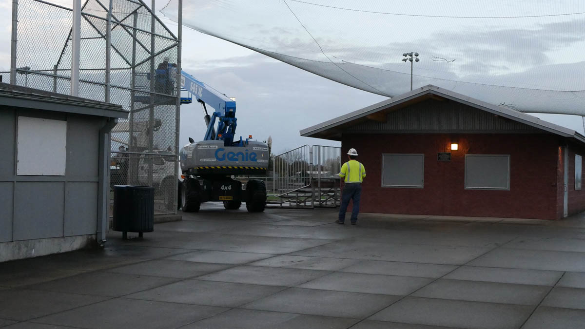 Workers prepare to raise a platform over the top of the SHS light pole